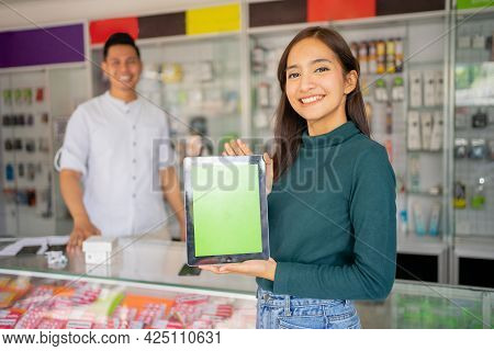 Smiling Woman Holding A Tablet With A Male Shop Assistant