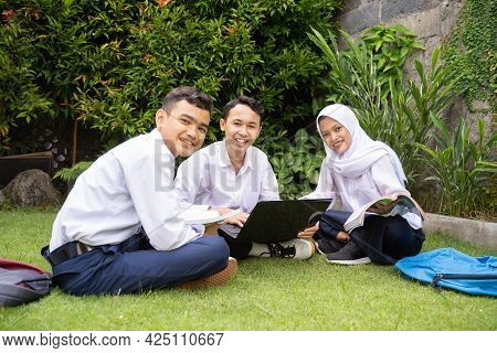 Three Teenagers Smile At The Camera In School Uniform Studying Together Using A Laptop