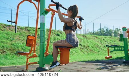 Side View Of Fit Woman Practicing Wide Grip Lat Pulldowns Using Simulator At Sports Ground. Stunning