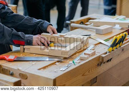 Professional Man Carpenter Working With Wooden Detail - Assembling Process: Close Up. Carpentry Work