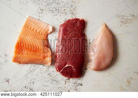 Fresh raw beef steak, chicken breast, and salmon fillet
