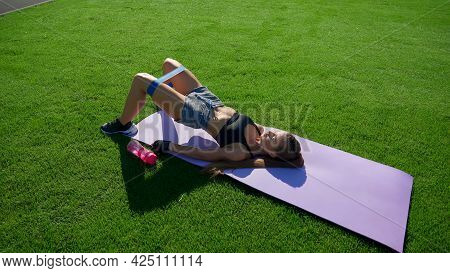 Young Woman With Perfect Muscular Body Training Glutes Using Fitness Resistance Band On Mat On Green