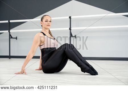 Graceful Flexible Attractive Woman Posing On Floor, Looking At Camera And Smiling. Side View Of Chee