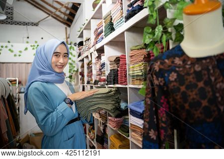 A Veiled Business Woman Piles Up A Pile Of Clothes On A Clothes Rack