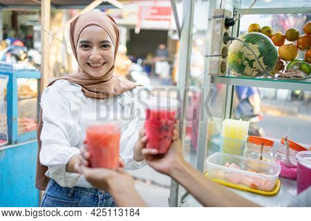 A Pretty Girl In A Head Scarf Smiles At The Camera As She Picks Up Two Cups Of Fruit Ice