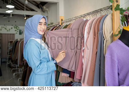 A Veiled Girl Holds Clothes To Offer While Standing
