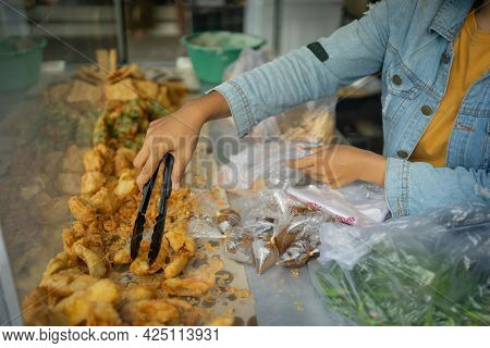 The Seller Uses Tong Tongs To Select And Pick Up The Fried Foods Before Inserting The Plastic Bag