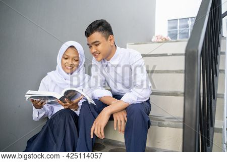 A Couple Of Asian Teenagers In Junior High School Uniforms Study Together Using A Book