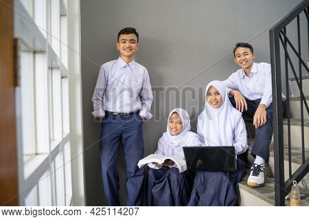 Four Teenagers In Junior High School Uniforms Smile At The Camera While Holding A Laptop And A Book