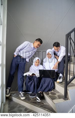 Four Teenagers In Junior High School Uniforms Share A Laptop
