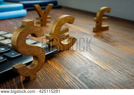 Global Economic And Currency Exchange. Symbols Of World Currencies On The Table.