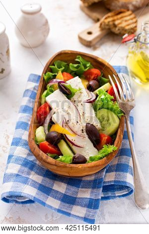 Fresh Greek Salad With Tomato, Cucumber, Bel Pepper, Olives And Feta Cheese On Wooden Plate. Traditi