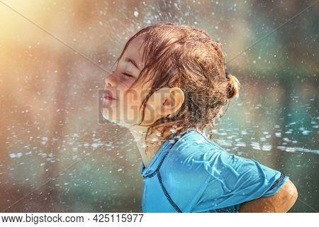 Little Cheerful Baby Boy Enjoying Refreshing Shower on the Beach. Playing with a Water. Having Fun in Aquapark on the Beach resort.