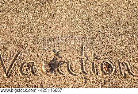 Word Vacation Written In The Sand On The Beach.  Summer Travel Concept. Vacation Holidays Background