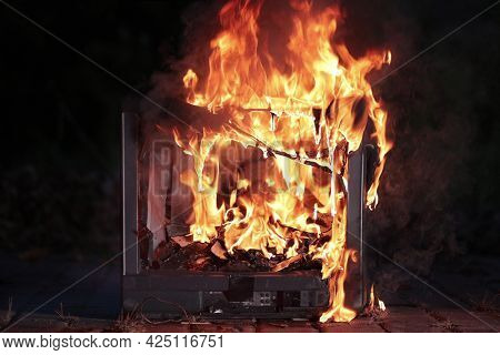 Old Tube TV set burning in flames, plastic melting a dripping around broken CRT screen