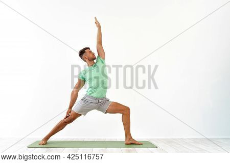 Attractive Young Man Practicing Advanced Yoga On White Background. A Series Of Yoga Poses. For Good