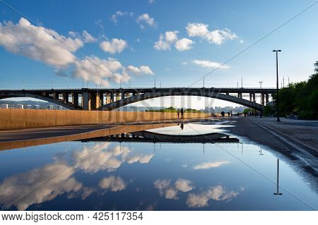 The Sky And The Communal Bridge Are Reflected In A Rain Puddle. Urban Landscape Of The City Of Krasn