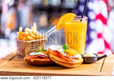 Sandwich with fried egg, french fries and orange juice breakfast served in american restaurant