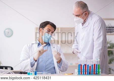 Two male chemists working at the lab during pandemic