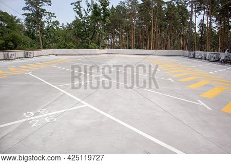 Empty Rooftop Parking. Directional Traffic Arrows And Parking Spots Are Marked With White And Yellow