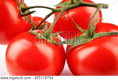 Ripe Juicy Red Tomatoes On A Branch.