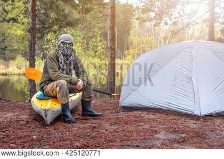 Tough Guy Sit Near The Tent And His Kayak In The Forest On The River Bank. Outdoor Camping Tent Conc