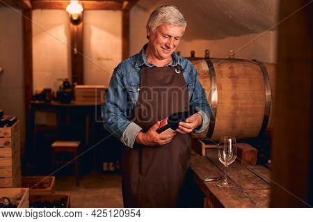 Joyful Man With Bottle Of Wine Standing In Wine Cellar