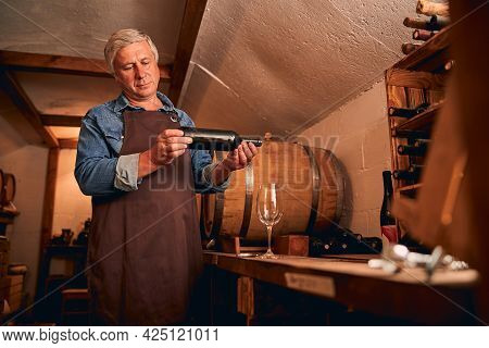 Handsome Man With Bottle Of Wine Standing In Wine Cellar