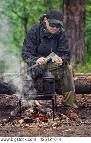 Tough Guy In Black Glasses And Harsh Clothes Peeling Potatoes Near The Fire With An Black Ax. Outdoo