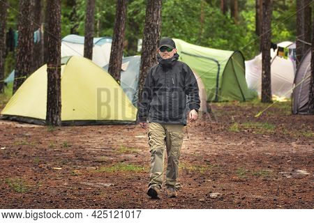 Tough Guy Walking Near The Camping Tents In The Forest On The River Bank. Outdoor Camping Concept