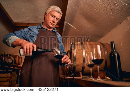 Calm Concentrated Man Pouring Red Wine In The Cellar