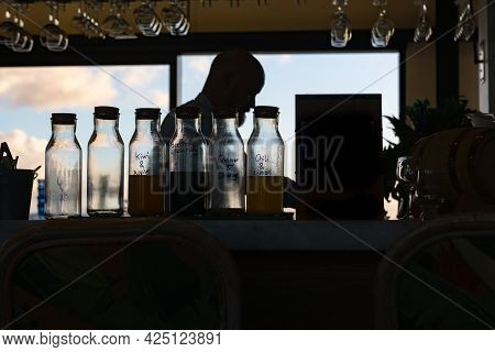 Auckland New Zealand - June 17 2021;bottles Of Syrup Mixes On Bar In Front Of Silhouette Of Barman B