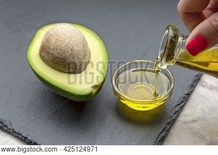 Avocado Oil. An Avocado With A Bone Lies On A Stone Tray. Avocodo Oil Is Poured Into A Plate. Banner