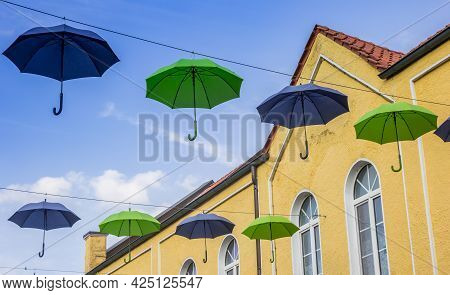 Colorful Umbrellas In Front Of A Yellow Building In Meppen, Germany