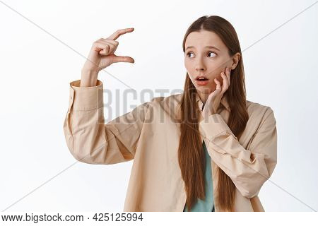 Girl Looks Troubled At Small Tiny Size, Showing Little Thing And Staring Worried At Product On Copy