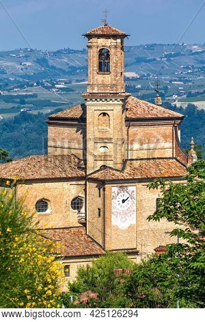 View of narrow road and old brick church in small town of Guarene in Piedmont, Northern Italy.