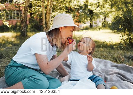 Family Picnic Outdoors. Beautiful Young Mother In A Hat Eating A Peach With Her Baby. Mom And Son Ar