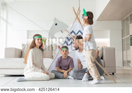 Happy Family Of Parents And Two Children Playing Indian At Home, Wigwam Tent, Toy Horse, Feather Roa