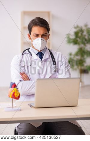Young male doctor cardiologist working in the clinic during pand