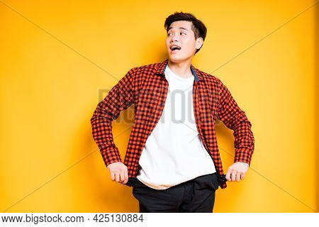Happy Asian Guy In Shirt Twisting Empty Pockets Out Of Trousers With His Hands Looking Up