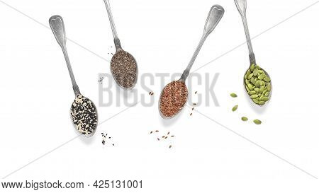Various Seeds In Spoons Isolated On White Background. Pumpkin, Flax, Sesame And Chia Seeds. Top View