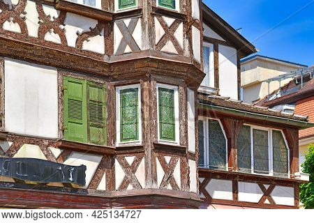 Oriel And Windows With Green Shutters Of Old European Style Half Timbered Frame House