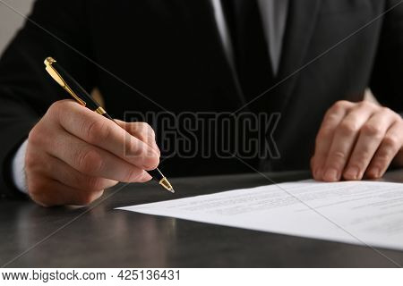 Male Notary Signing Document At Table, Closeup