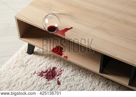 Overturned Glass And Spilled Red Wine On White Carpet Indoors
