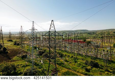 Drone Flying Over Agricultural Land And Electric High Voltage Pylon Against Beautiful Sky. Farmer Fe