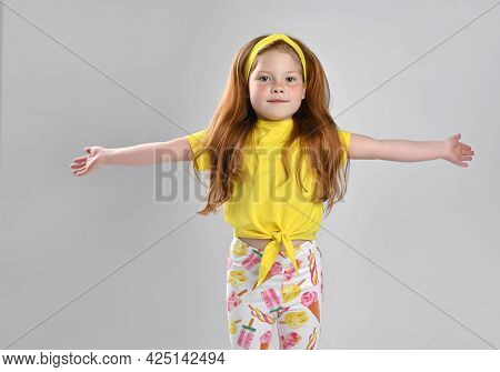 Little Red-haired Girl Child With Serious Emotion Widely Spreading Arms Ready To Hug. Redhead Charmi