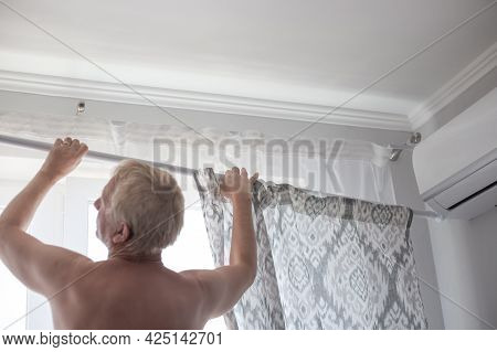An Adult Man Hangs A Curtain With A Curtain On The Window. Household Chores And New Renovation.