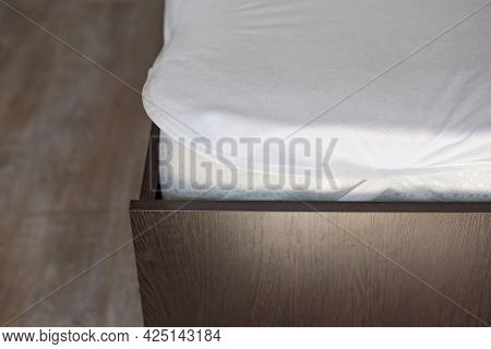 Wooden Bed With A High Mattress And A Covered White Mattress Cover.