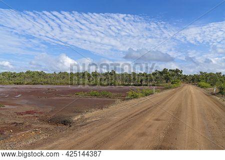 Dirt Road Beside Salt Flats And Bushland Under A Cloudy Blue Sky