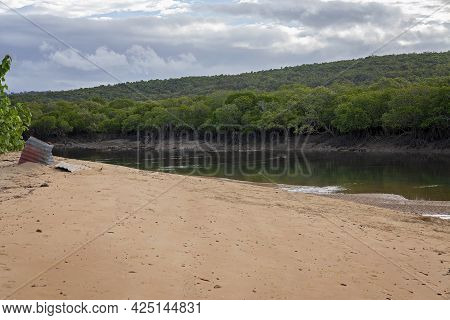 Creek At Low Tide With Mud And Sandbanks Visible And A Bushland Shoreline Under A Cloudy Sky
